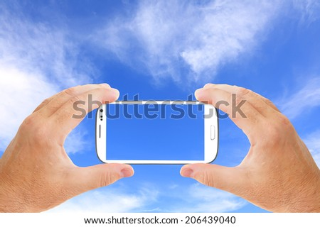 Hands holding touch screen smart phone and taking blue and white sky picture (video) - stock photo
