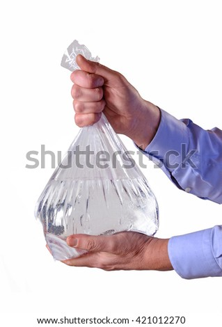 Hands holding transparent plastic water bag on white background. - stock photo