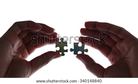 Hands holding two pieces of puzzle with white background. - stock photo