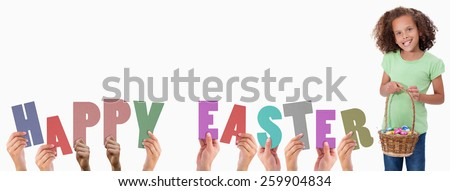 Hands holding up happy easter against portrait of a young girl holding a basket full of easter eggs - stock photo