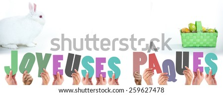 Hands holding up joyeuses pasques against white bunny facing basket of easter eggs - stock photo