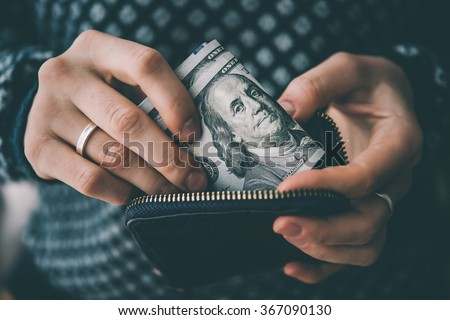 Hands holding us dollar bills and small money pouch. Toned picture - stock photo