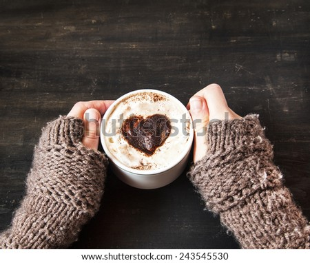 Hands Holding Warm Cappuccino with Froth and Cocoa Heart Shape  - stock photo