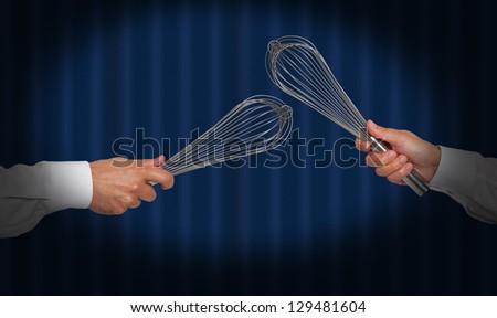 Hands holding whisks under a spot light - stock photo