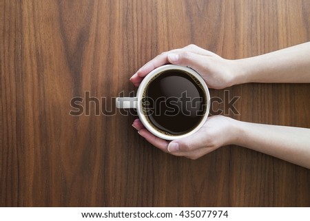 hands holding white coffee cup and hot espresso coffee on wooden table. top view - stock photo