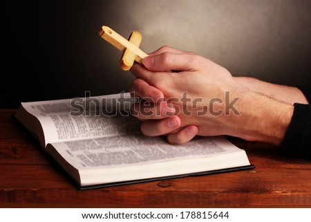 Hands holding wooden cross over open russian holy bible on grey background - stock photo
