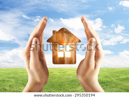 hands holding wooden home on field background - stock photo