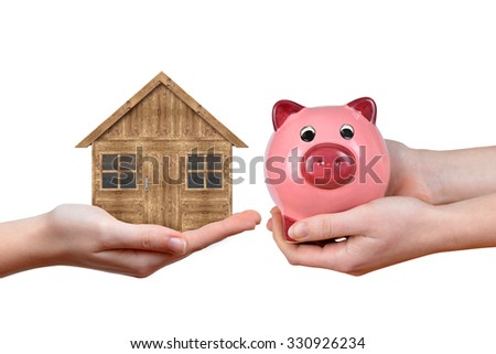 Hands holding wooden house and pink piggy bank on white background. Concept of saving for housing
