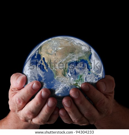 Hands holding world with isolated black background. Earth image courtesy of NASA.