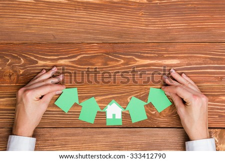 Hands hplding green paper house figure models arrows on grunge rustic wooden background. Concept for comparision of real estate houses pricing Real Estate Concept. Top view, copy space. Eco house - stock photo