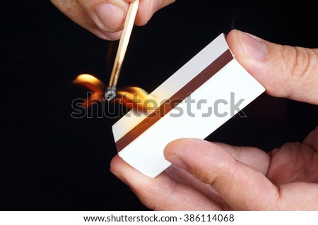 Hands igniting a matchstick on matchbox, isolated on black background.  - stock photo