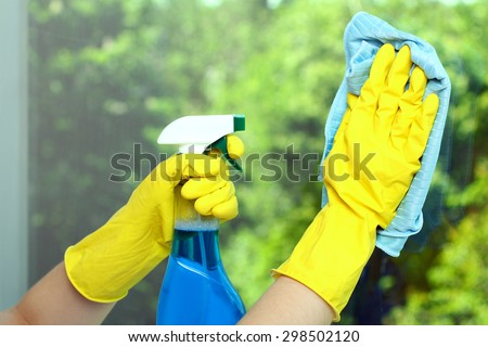 Hands in a yellow glove wiping  window with napkin and the cleaning fluid on the background of trees - stock photo