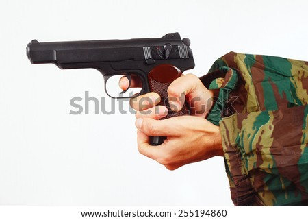 Hands in camouflage uniform with automatic army pistol on a white background - stock photo