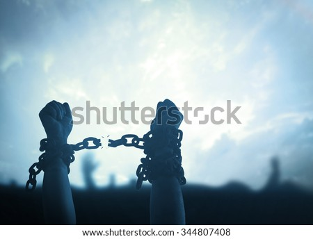 Hands in chains over blurred sunset background. Day for the Abolition of Slavery Victory Free World Press Freedom Amnesty Load World Refugee Dark War concept. - stock photo