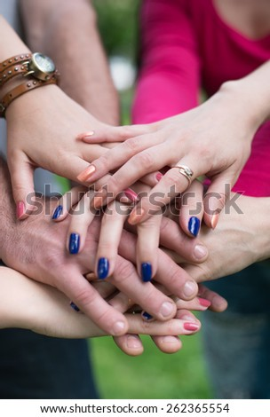 Hands in. Closeup of pile of hands of a business team showing unity - stock photo