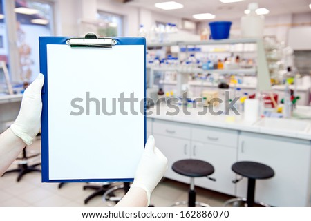 Hands in gloves holding a blank card with laboratory results. At background blurred laboratory. - stock photo