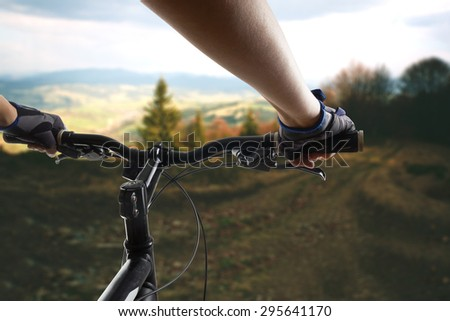 Hands in gloves holding handlebar of a bicycle. Mountain Bike cyclist riding single track. Healthy lifestyle active athlete doing sport - stock photo