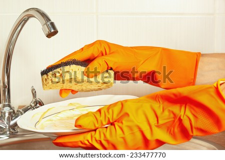 Hands in gloves with dirty plate over the sink in the kitchen - stock photo