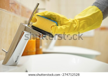 hands in gloves with sponge cleaning pipe and  faucet - stock photo