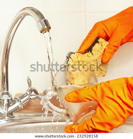 Hands in gloves with sponge wash the glass under running water  - stock photo