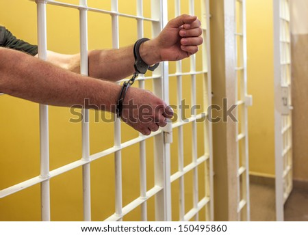 Hands in handcuffs protrude through the bars. - stock photo