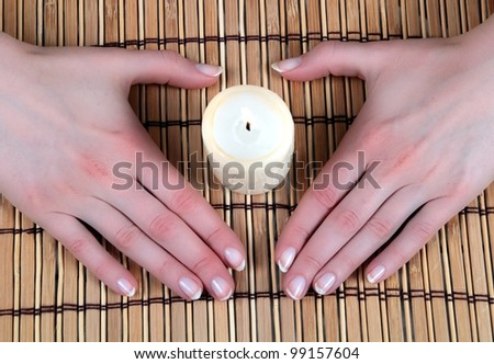 Hands in heart-shape covering a candle over bamboo mat - stock photo
