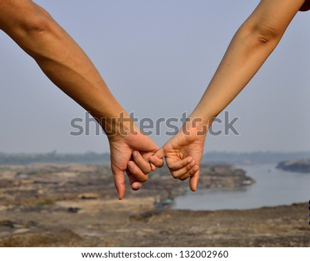 Hands in heart shape with silhouette and shadow with sun in background