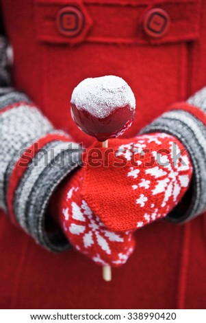hands in mittens holding an apple with red caramel apple in sugar - stock photo