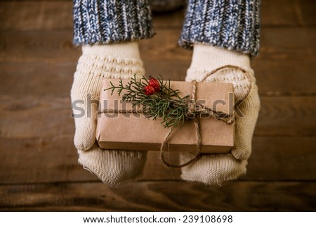 Hands in mittens holding gift box - stock photo
