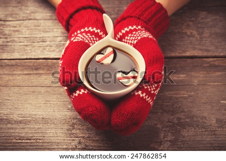 Hands in mittens holding hot cup of coffee with marshmallow hearts on wooden background