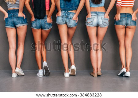 Hands in pockets. Close-up rear view of five women wearing jeans shorts and holding hands in their pockets while standing against grey background - stock photo