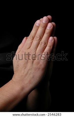 Hands in prayer on dark background - stock photo