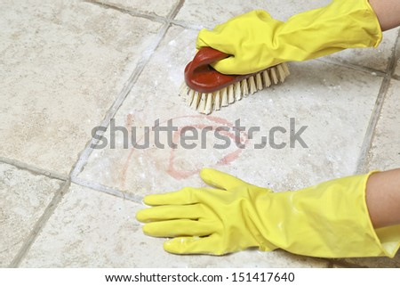 hands in rubber gloves scrubbing the tiles - stock photo