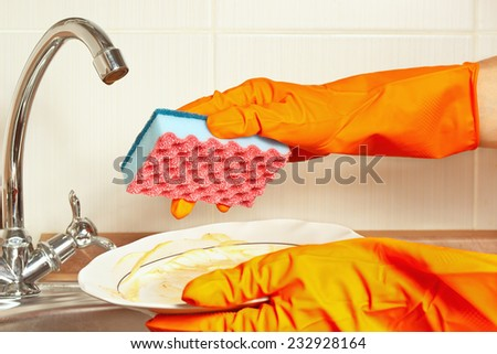 Hands in rubber gloves with dirty dishes over the sink in the kitchen - stock photo