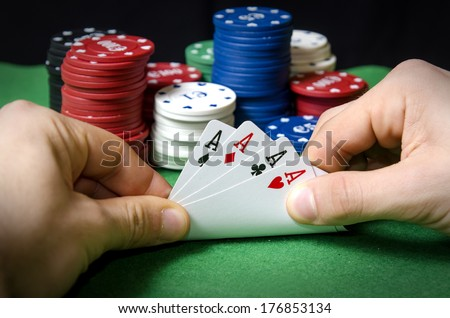 Hands in the foreground with Poker aces - stock photo