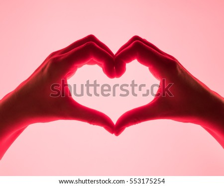 Hands in the form of heart red background. heart symbol with hand. valentines day card. Woman's hands silhouette in form of heart. hand Gestures