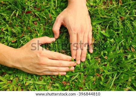 Hands in the grass in the form of heart