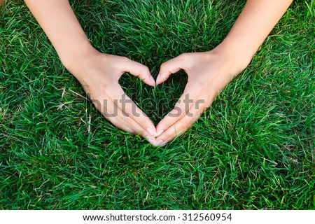 Hands in the grass in the form of heart.hands holding green heart shaped grass/ green baby plants arranged in a heart shape / love nature / save the world / heal the world / environmental preservation - stock photo