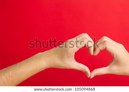 Hands in the shape of heart isolated on red background - stock photo