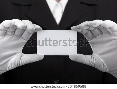 Hands in white gloves holding a plastic card - stock photo