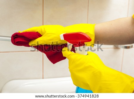 Hands in yellow gloves holding special rag and spray for cleaning faucet. Cleaning concept.