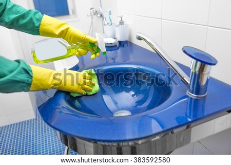Hands in yellow gloves washing the sink with detergent.