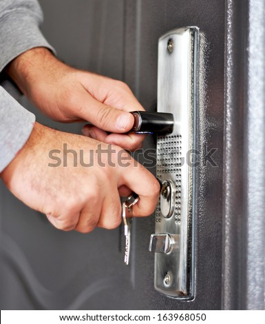 Hands inserting keys in door lock - stock photo