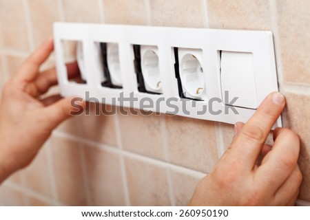 Hands installing decorative frame on electrical sockets in the wall - closeup - stock photo