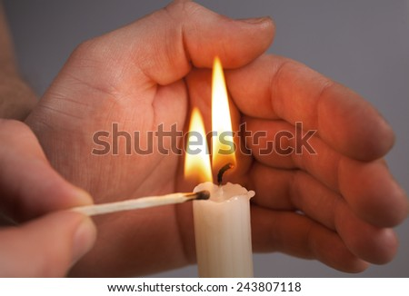 Hands Kindle candle - stock photo