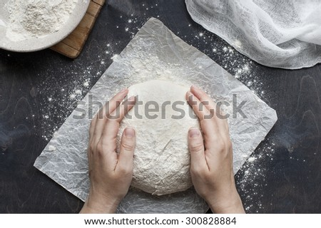 Hands knead the dough - stock photo