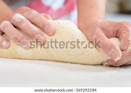 hands knead the dough and cook - stock photo