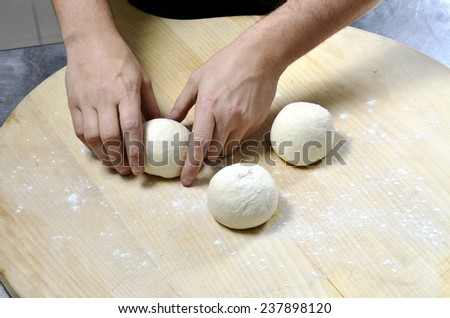 Hands knead the dough balls for pizza or bread making - stock photo