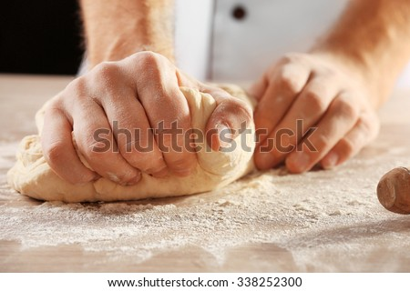Hands kneading dough for pizza on the wooden table, close-up - stock photo