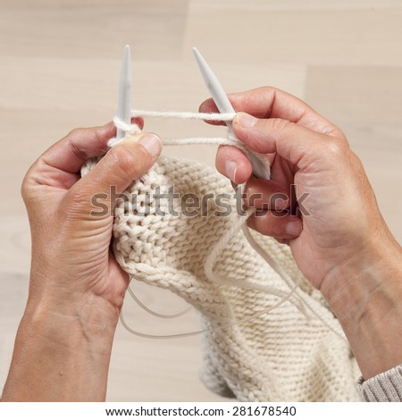 Hands knitting white scarf, pullover